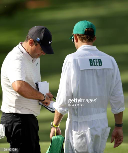 Patrick Reed of the United States talks with his caddie Kessler Karain on the second green during a practice round prior to the Masters at Augusta...