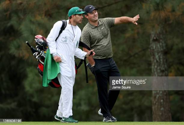 Patrick Reed of the United States talks with his caddie Kessler Karain on the 15th hole during the continuation of the second round of the Masters at...