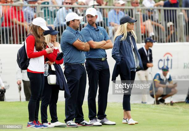 Patrick Reed of the United States team, his wife Justine Karain, and Webb Simpson of the United States team and his wife Taylor Dowd Simpson, look on...