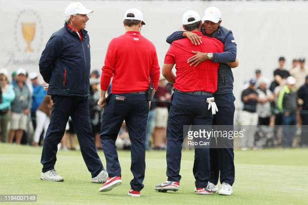 Patrick Reed of the United States team is congratulated by Playing Captain Tiger Woods of the United States team, Assistant Captain Zach Johnson of...