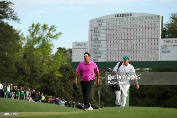 Patrick Reed of the United States walks onto the 18th green with caddie Kessler Karain during the final round of the 2018 Masters Tournament at...