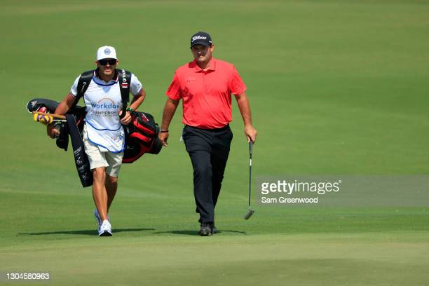 Patrick Reed of the United States walks with caddie Kessler Karain on the second hole during the final round of World Golf Championships-Workday...
