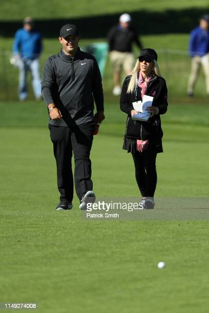 Patrick Reed of the United States walks with wife Justine Karain during a practice round prior to the 2019 PGA Championship at the Bethpage Black...
