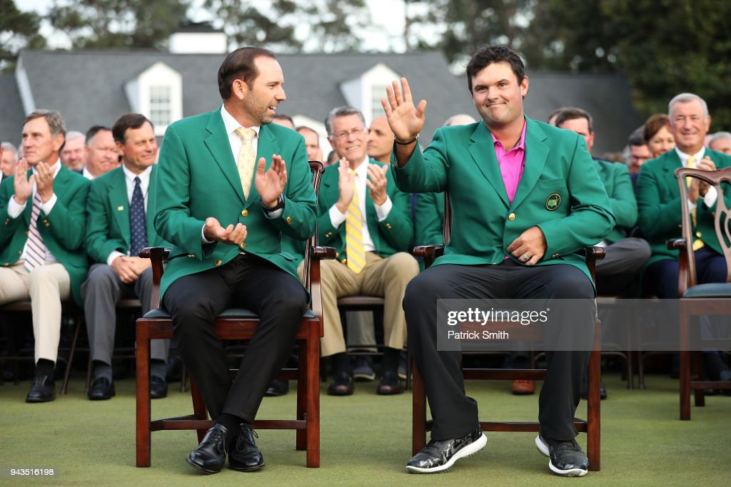 Patrick Reed (R) of the United States waves after being presented with the green jacket by Sergio Garcia (L) of Spain after winning the 2018 Masters Tournament at Augusta National Golf Club on April 8, 2018 in Augusta, Georgia.