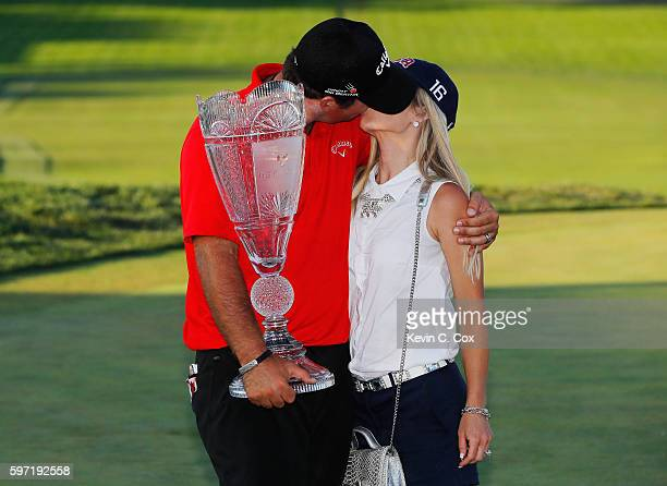 Patrick Reed poses with his wife Justine and the trophy after winning The Barclays in the PGA Tour FedExCup PlayOffs on the Black Course at Bethpage...