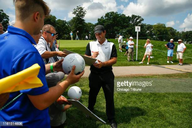 Patrick Reed signs items for spectators near the 1st hole during practice at Medinah Country Club in Medinah Ill on Tuesday Aug 13 2019 The BMW...