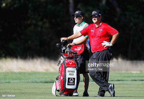 Patrick Reed waits alongside his caddie Kessler Karain on the 12th hole during the final round of The Barclays in the PGA Tour FedExCup PlayOffs on...