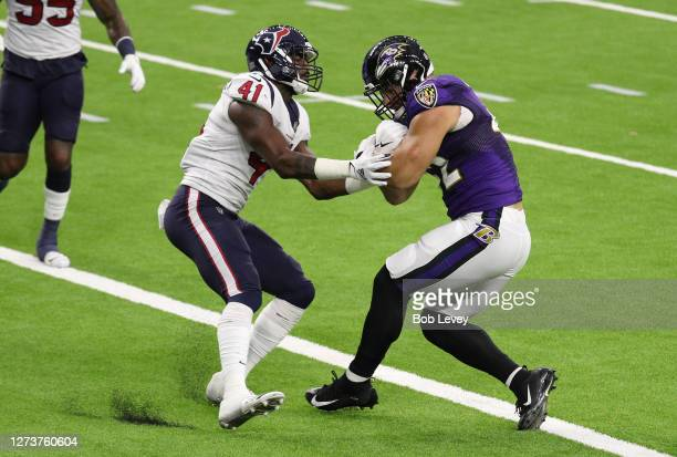Patrick Ricard of the Baltimore Ravens scores a touchdown against Zach Cunningham of the Houston Texans during the first half at NRG Stadium on...