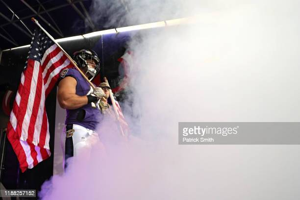 Patrick Ricard of the Baltimore Ravens waits to take the field while holding an American flag before playing against the Houston Texans at MT Bank...