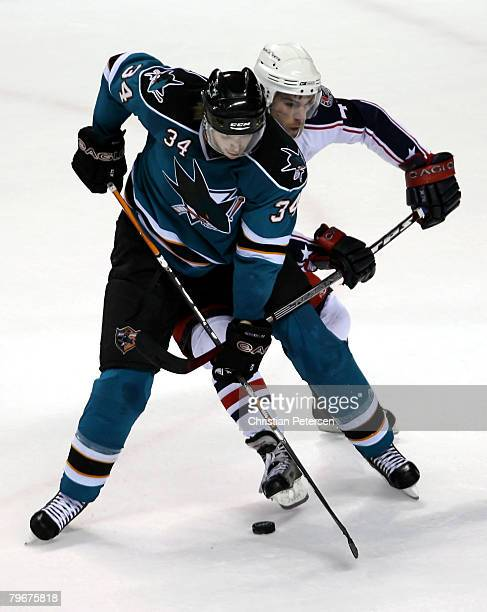 Patrick Rissmiller of the San Jose Sharks draws a hooking penalty on Dan Fritsche of the Columbus Blue Jackets during overtime of the NHL game at HP...