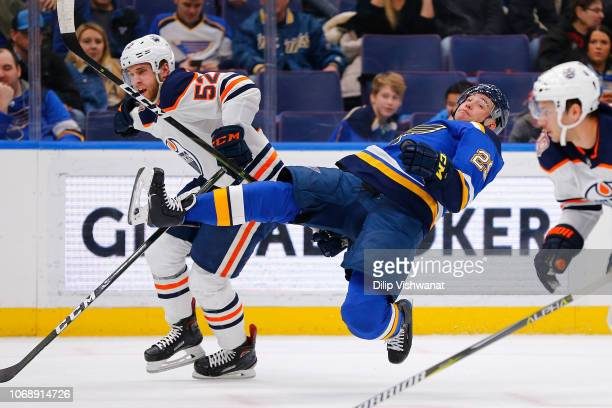 Patrick Russell of the Edmonton Oilers trips Vince Dunn of the St. Louis Blues at the Enterprise Center on December 5, 2018 in St. Louis, Missouri.