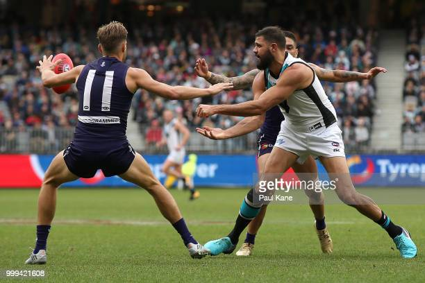 Patrick Ryder of the Power handballs during the round 17 AFL match between the Fremantle Dockers and the Port Adelaide Power at Optus Stadium on July...