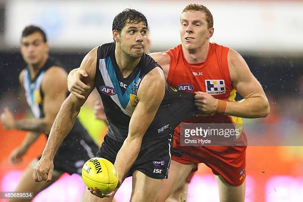 Patrick Ryder of the Power handballs during the round 22 AFL match between the Gold Coast Suns and the Port Adelaide Power at Metricon Stadium on...