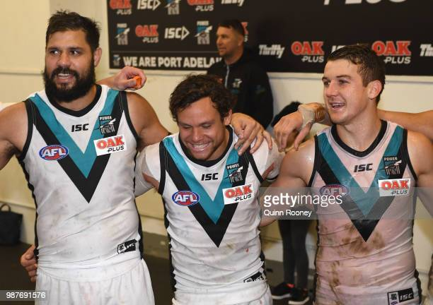 Patrick Ryder Steven Motlop and Jack Trengove of the Power sing the song in the rooms after winning the round 15 AFL match between the Carlton Blues...
