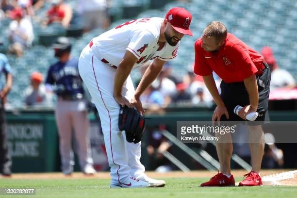 Patrick Sandoval of the Los Angeles Angels is checked on during the first inning against the Seattle Mariners at Angel Stadium of Anaheim on July 18,...