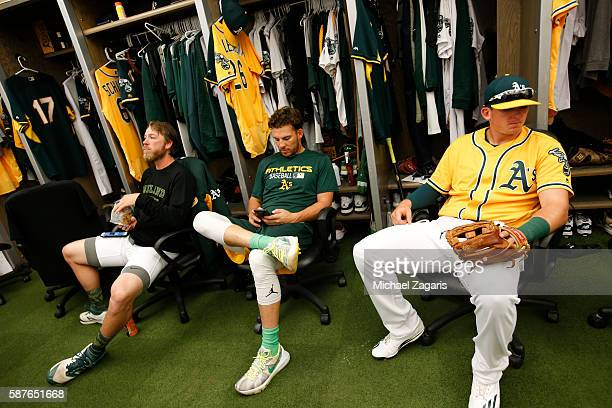 Patrick Schuster Danny Valencia and Ryon Healy of the Oakland Athletics relax in the clubhouse prior to the game against the Houston Astros at the...