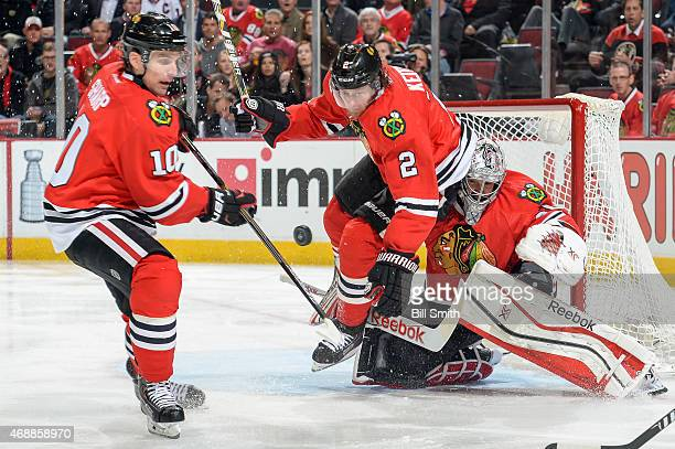 Patrick Sharp and Duncan Keith of the Chicago Blackhawks lunge for the puck next to goalie Corey Crawford during the NHL game against the Minnesota...