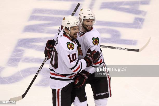Patrick Sharp and Troy Brouwer of the Chicago Blackhawks celebrate a third period goal by Brouwer while taking on the San Jose Sharks in Game Two of...