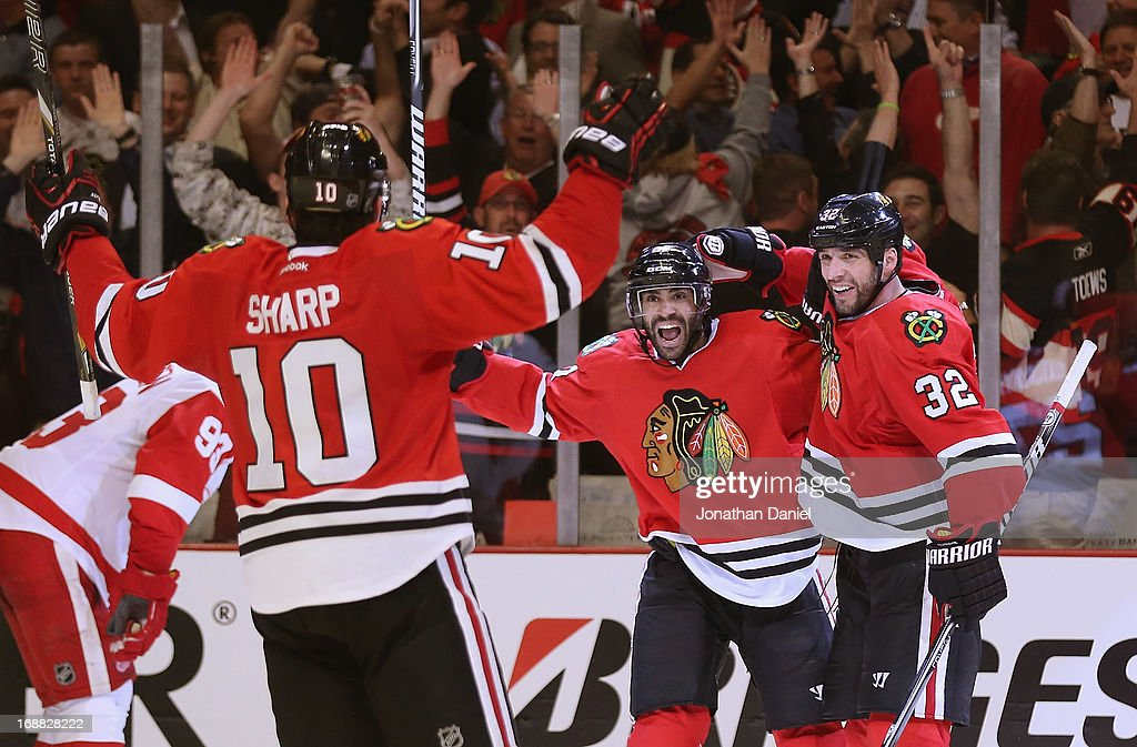 Patrick Sharp #10, Johnny Oduya #27 and Michal Rozsival #32 of the Chicago Blackhawks celebrate Oduyas' third period goal against the Detroit Red Wings in Game One of the Western Conference Semifinals during the 2013 NHL Stanley Cup Playoffs at the United Center on May 15, 2013 in Chicago, Illinois. The Blackhawks defeated the Red Wings 4-1.