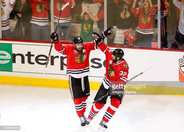 Patrick Sharp of the Chicago Blackhawks celebrates with teammate Michal Rozsival after scoring a goal in the first period against Tuukka Rask of the...