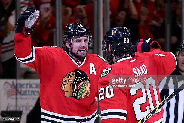 Patrick Sharp of the Chicago Blackhawks celebrates with teammate Brandon Saad after scoring a goal against Jonathan Quick of the Los Angeles Kings in...