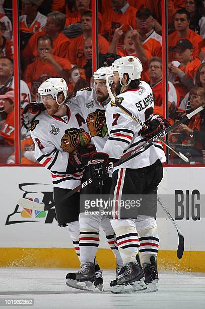 Patrick Sharp of the Chicago Blackhawks celebrates with teammates Duncan Keith and Brent Seabrook after scoring a goal in the second period against...