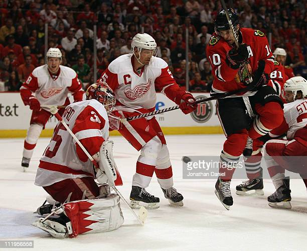 Patrick Sharp of the Chicago Blackhawks hops out of the way of the puck as Jimmy Howard of the Detroit Red Wings makes a save and Nicklas Lidstrom...