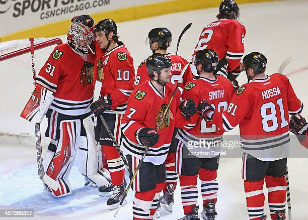 Patrick Sharp of the Chicago Blackhawks hugs Antti Raanta as teammates line up for congratulations following a win over the Philadelphia Flyers at...