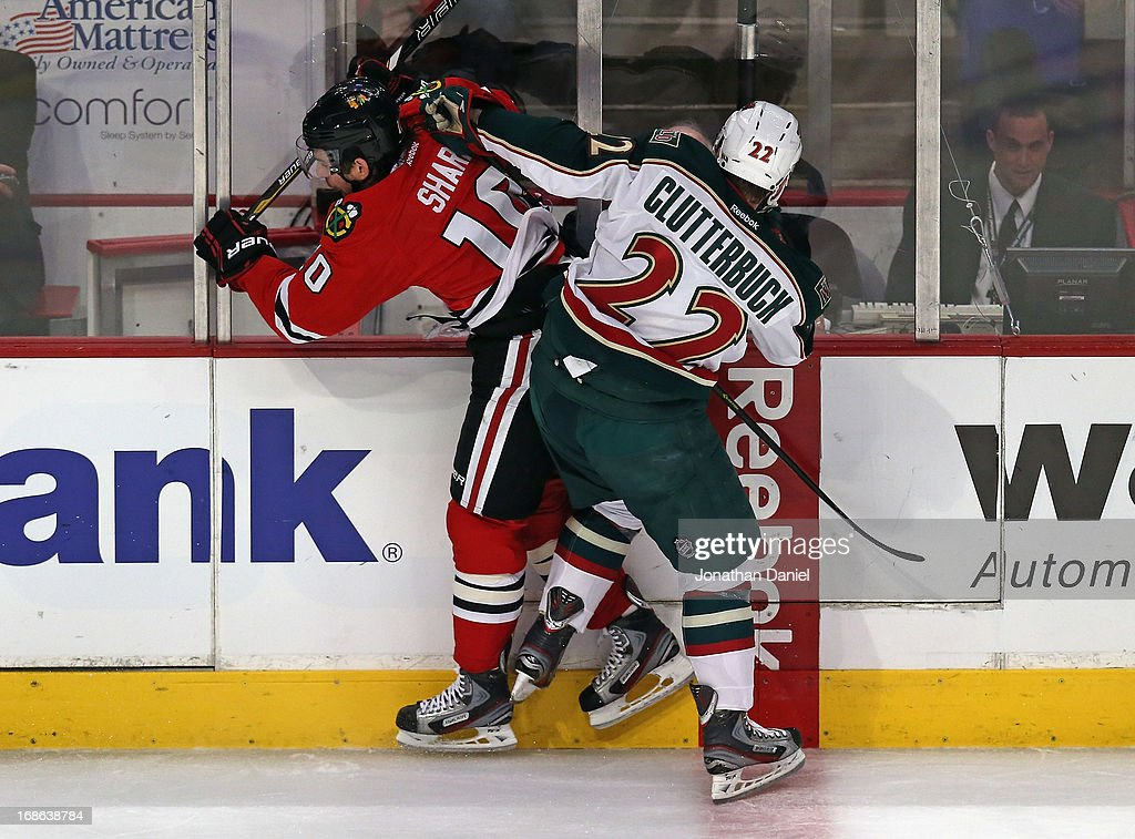Patrick Sharp #10 of the Chicago Blackhawks is checked by Cal Clutterbuck #22 of the Minnesota Wild in Game Five of the Western Conference Quarterfinals during the 2013 NHL Stanley Cup Playoffs at the United Center on May 9, 2013 in Chicago, Illinois. The Blackhawks defeated the Wild 5-1 to win the series.