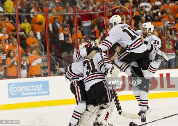 Patrick Sharp of the Chicago Blackhawks jumps for joy with teammates Andrew Ladd and Antti Niemi to celebrate after Patrick Kane scored the winning...