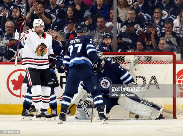 Patrick Sharp of the Chicago Blackhawks lifts his stick in celebration after scoring a second period goal against the Winnipeg Jets at the Bell MTS...