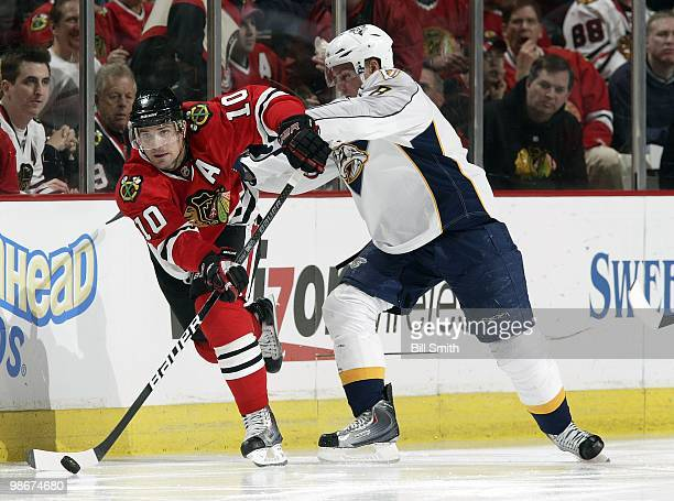 Patrick Sharp of the Chicago Blackhawks takes the puck up the ice as Kevin Klein of the Nashville Predators pushes from behind at Game Two of the...