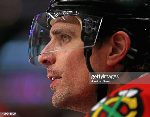 Patrick Sharp of the Chicago Blackhawks who scored three goal through two periods on his birthday watches teammates from the bench as they take on...