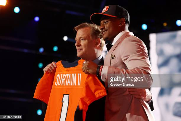 Patrick Surtain II poses with NFL Commissioner Roger Goodell onstage after being selected ninth by the Denver Broncos during round one of the 2021...