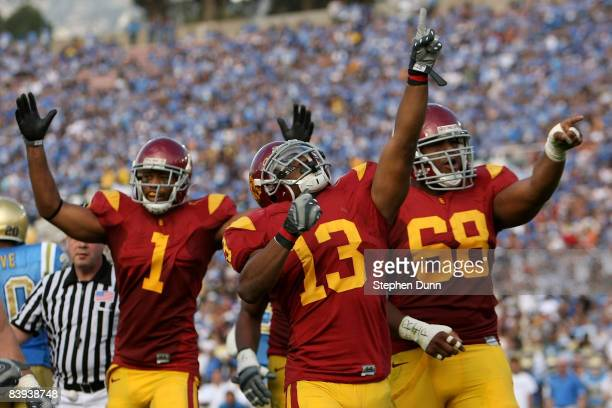 Patrick Turner, Stafon Johnson and Butch Lewis of the USC Trojans celebrate a touchdown by Johnson in the second quarter against the UCLA Bruins on...