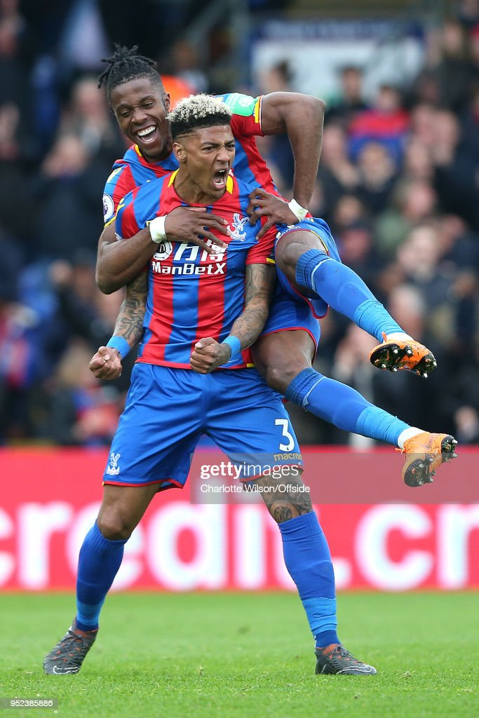 Patrick van Aanholt of Crystal Palace celebrates scoring their 4th goal as Wilfried Zaha of Crystal Palace jumps on his back during the Premier League match between Crystal Palace and Leicester City at Selhurst Park on April 28, 2018 in London, England.