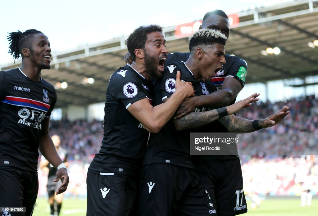 Patrick van Aanholt of Crystal Palcace celebrates scoring his side's second goal with team mates Andros Townsend and Christian Benteke during the Premier League match between Stoke City and Crystal Palace at Bet365 Stadium on May 5, 2018 in Stoke on Trent, England.