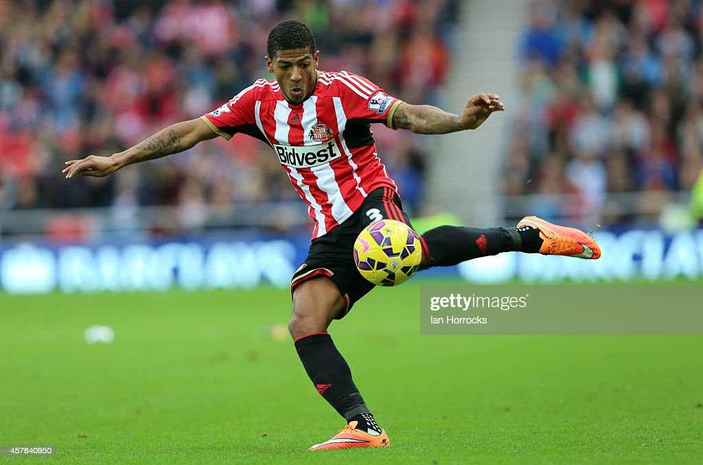 Patrick Van Aanholt tries a shot whilst Arsenal keeper Szczesny is off his line during the Barclays Premier League match between Sunderland AFC and Arsenal FC at The Stadium of Light on October 25, 2014 in Sunderland, England.