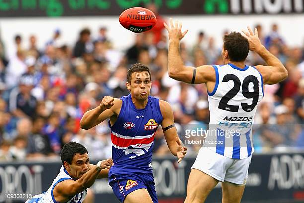 Patrick Veszpremi of the Bulldogs handballs under pressure during the Pool Six NAB Cup round one AFL match between the North Melbourne Kangaroos and...