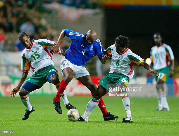 Patrick Vieira of France is crowded out by Salif Diao and captain Aliou Cisse of Senegal as Senegal defeat France 10 during the second half of the...