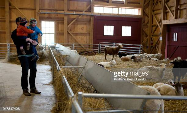 Patrick Walters of Portland holds up his sons Anders HoganWalters left and Lars HoganWalters to see the sheep before the First Time Farmers program...