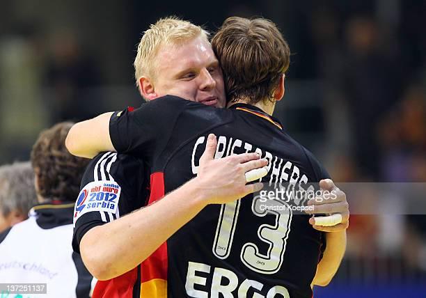 Patrick Wiencek embraces Sven-Soeren Christophersen of Germany after winning 24-23 the Men's European Handball Championship group B match between...