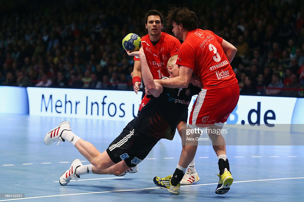 Patrick Wiencek (L) of Germany is challenged by Jonathan Stenbacken of Melsungen during a benefit match between the German national handball team and MT Melsungen at Rothenbach-Halle on March 5, 2013 in Kassel, Germany.
