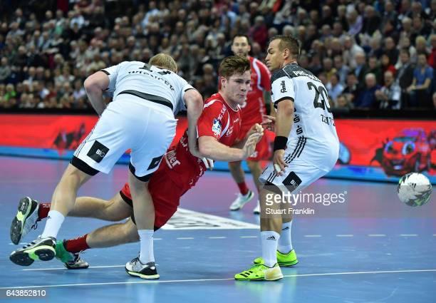 Patrick Wiencek of Kiel challenges Johhanes Golla of Melsungen during the DKB Handball Bundesliga game between THW Kiel and MT Melsungen at...