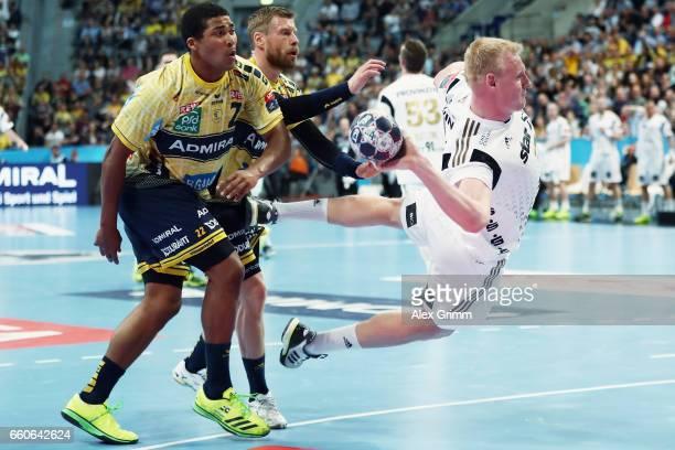 Patrick Wiencek of Kiel eludes Mads Mensah Larsen and Gudjon Valur Sigurdsson of RheinNeckar Loewen during the EHF Champions League Quarter Final Leg...