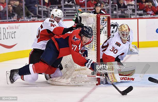 Patrick Wiercioch of the Ottawa Senators knocks down TJ Oshie of the Washington Capitals as he shoots on Andrew Hammond at the Verizon Center on...