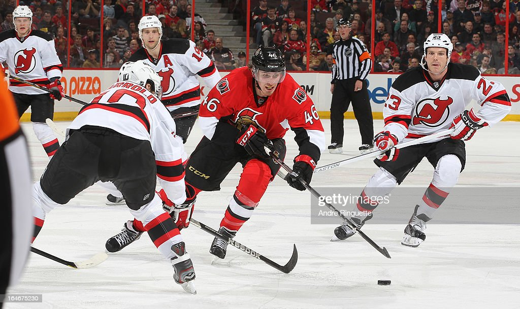 Patrick Wiercioch #46 of the Ottawa Senators stick handles the puck into the offensive zone against Peter Harrold #10 and David Clarkson #23 of the New Jersey Devils on March 25, 2013 at Scotiabank Place in Ottawa, Ontario, Canada.