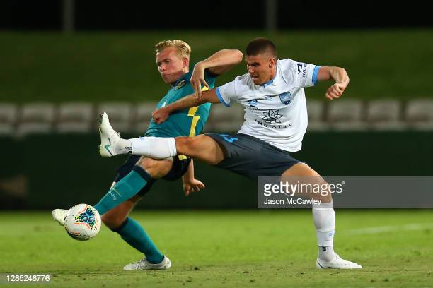 Patrick Wood of Sydney FC is challenged by Josh Laws of the Olyroos during the match between the Australian Under 23 Olyroos and Sydney FC at...