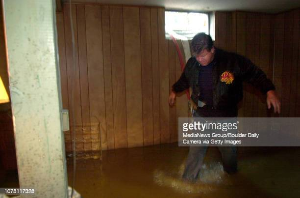 Patrick Wood with Utility Service of the City and County of Broomfield after bringing hoses through a window walks through the flooded basement of...