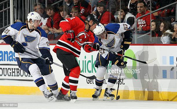Patrik Berglund and David Perron of the St Louis Blues defend against Dean McAmmond of the New Jersey Devils at the Prudential Center on March 20...